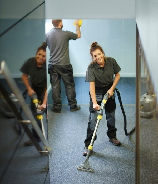 Man cleaning the walls \and another lady cleaning the floor.